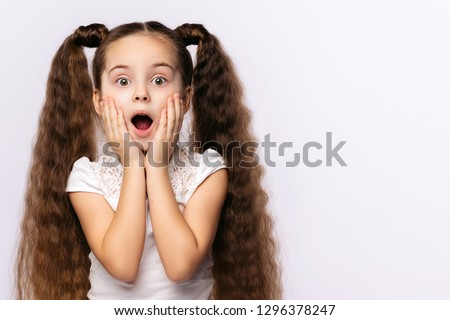 Little amazed girl opened her mouth, palms on cheeks at white background