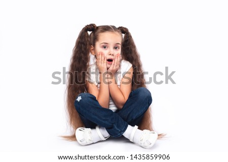 Little amazed girl opened her mouth, palms on cheeks at white background. Sitting on the floor.