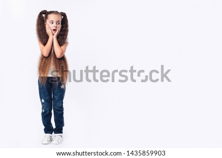 Little amazed girl opened her mouth, palms on cheeks. Looking down at copyspace. White background