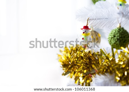 Little and cute snowman hanging on a Christmas Tree with some baubles in the background