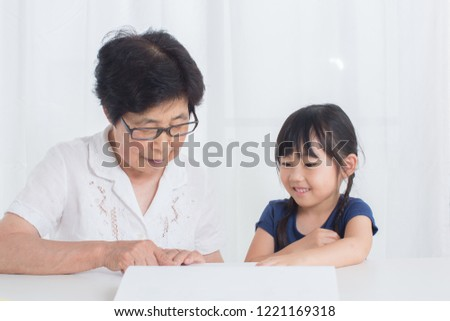 little and old asian reading picture book