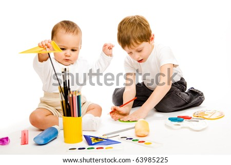 Little and preschool brothers drawing, isolated