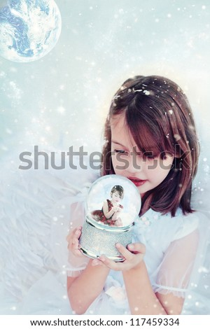 Little angel holds a snow globe and watches a little girl inside blowing snow. - stock photo