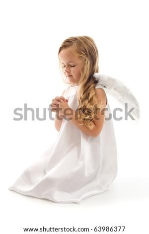 Little angel praying kneeling on the floor - isolated