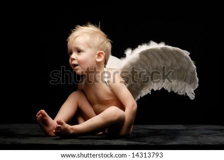 Little angel sitting sideways against black background legs bent month open