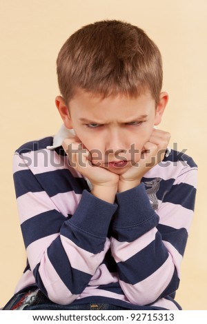 Little angry boy isolated on neutral background. Facial expressions concept. - stock photo