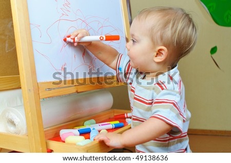 stock photo : Little artist. Cute one and half year old boy draws markers