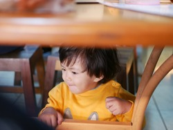 Little Asian baby girl sitting and playing / exploring under a dinning table during a meal with her family at a restaurant - toddler behaviours at mealtime