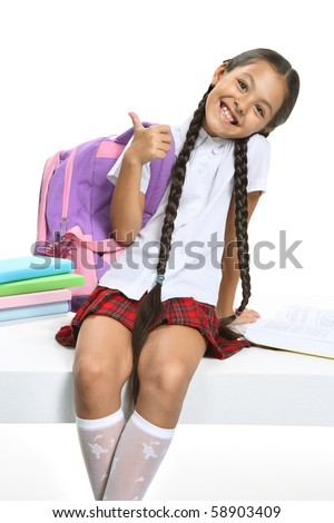 Little Asian beautiful girl in school uniform sitting on white