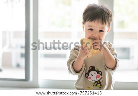 Little asian boy eating whole wheat bread at home., Background. Copy space.