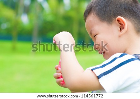 Little Asian boy playing bubbles wand at outdoor