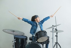 Little Asian boy plays the drums in studio with state of excitement against light gray background