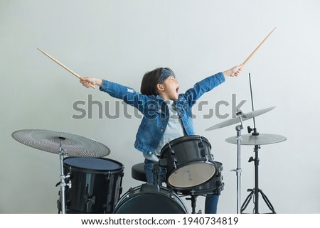 Little Asian boy plays the drums in studio with state of excitement against light gray background Stockfoto ©