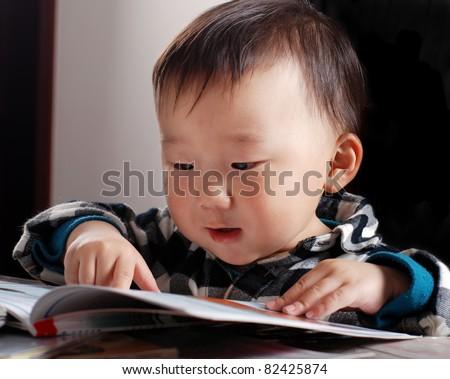 little asian boy reading book