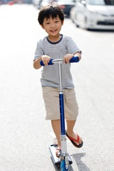 Little Asian boy riding scooter on the street