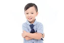 Little asian boy smiles over white background