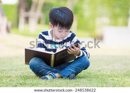 little asian boy writes homework in the garden