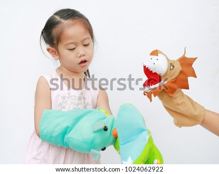 Little Asian child girl hands playing Rhinoceros, Lion and Crocodile puppets on white background. Educations concept.