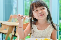 Little asian child girl having breakfast at the morning with a happy smiling face