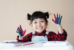 Little Asian child girl with colorful hands painted. Creative kid girl love art concept.