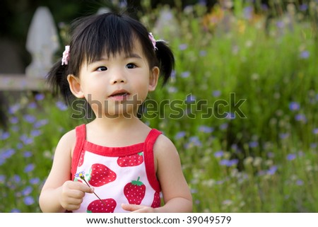 Little Asian child hold a flower in her hand