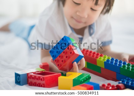 Stock Photo Little asian child playing with colorful construction blocks on white bed with copy space on left