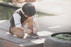 little asian child tying his shoes outdoors,vintage filter
