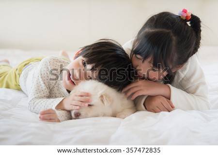 Little asian children and puppy having fun lying in bed