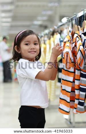 little asian cute girl shopping for a shirt