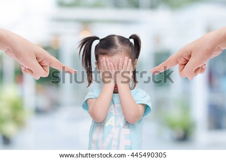 Little asian girl close her face by hands and crying while parents scold her at home. #445490305