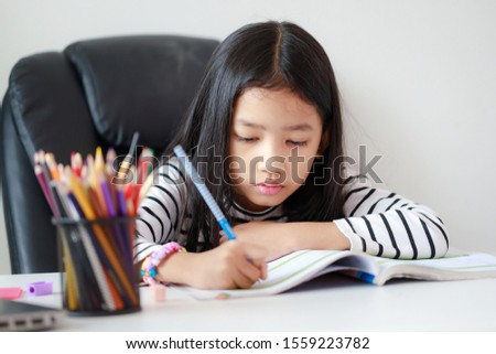 Little Asian girl doing homework for self learning and education concept select focus shallow depth of field