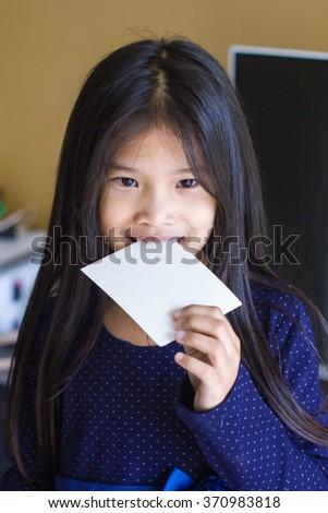 little Asian girl dressed in blue bites snack #370983818