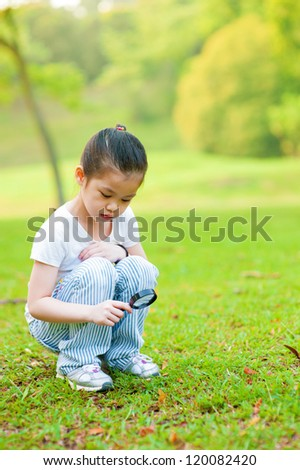 Little Asian girl exploring nature by magnifier