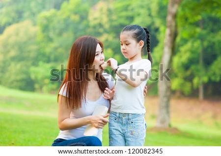 Little Asian girl feeding her mother sandwich outdoor