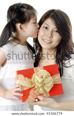 Little Asian girl giving gift for mother and kissing on mother's cheek