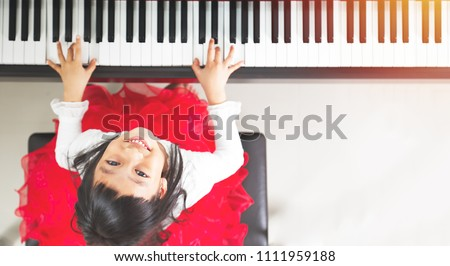 Little asian girl happy to play piano #1111959188