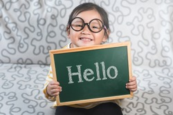 Little asian girl holding a chalkboard with a word HELLO. Concept of Hello day, Greetings, Introduction and lifestyle