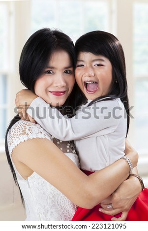 Little asian girl hugs her mother while smiling and looking on camera at home #223121095