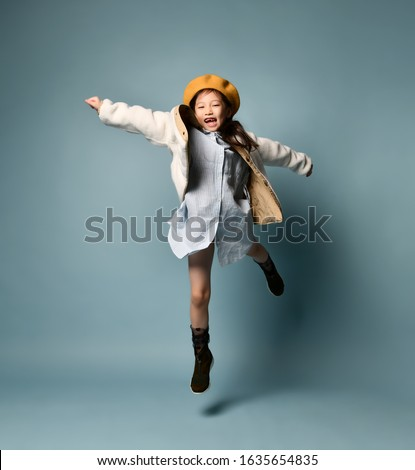 Little asian girl in a double-sided jacket, dress shirt, brown beret, boots. She laughs loudly with her toothless mouth, bouncing against a blue studio background. Childhood, fashion, hipster style.