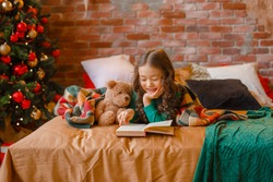 little Asian girl in pajamas in the bedroom lying on the bed near the Christmas tree reading a book with a Teddy bear Christmas, new year