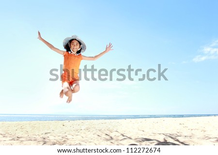 little asian girl jumping and having fun in the beach