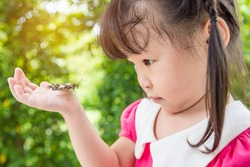 Little asian girl looking at butterfly on her hand in park,child and nature concept.