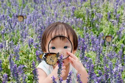 Little Asian girl looking at butterfly with magnifying glass in