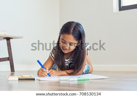 Little asian girl lying on floor painting with colored marker. Cute indian girl lying on the floor drawing in the living room at home. Lovely multiethnic child drawing.