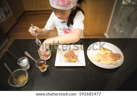 Little Asian girl penjoy decorate pancake with with decorate sugar pill in real life kitchen. #592685477