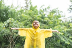 little asian girl play in autumn rain. kid playing on the nature outdoors. girl is wearing yellow raincoat and enjoying rainfall. family walk in the park. family walk in the park.