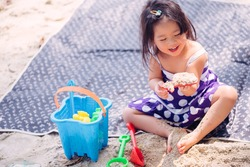 Little asian girl playing on the beach.Vacation and relax concept.
