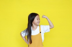 Little asian girl raising hand up showing his muscle isolated on yellow background. Child in dungarees with good health concept