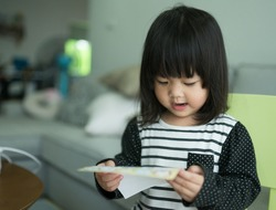 Little asian girl reading a letter from her father in home