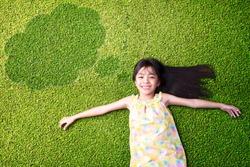 Little asian girl resting on green grass